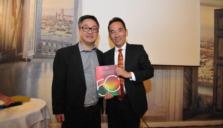 Coordenador do Evento, Claudio Kurita entrega livros dos 50 Anos da associação para o cônsul Akira Kusunoki (Jiro Mochizuki)